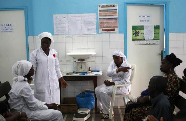 Nurses talk near a poster (C) displaying a government message against Ebola, at a maternity hospital in Abidjan, Ivory Coast, August 14, 2014. REUTERS/Luc Gnago