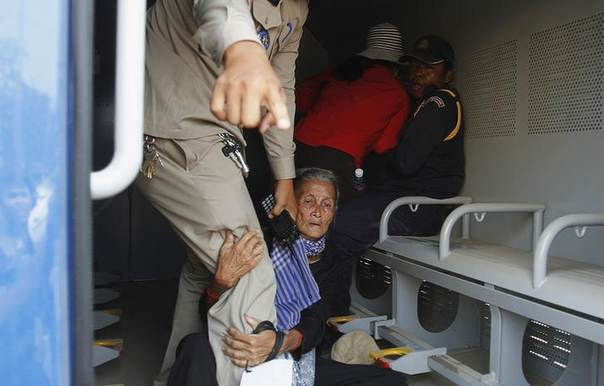 An elderly woman grabs the leg of a police officer as residents of Boeung Kak Lake community are arrested during a protest in Phnom Penh against a real estate development firm. Picture March 13, 2013. REUTERS/Samrang Pring