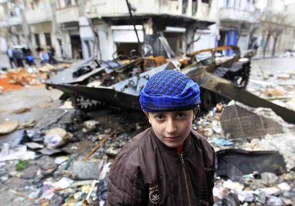 A Syrian boy stands in front of a damaged armoured vehicle belonging to the Syrian army in a street in Homs January 23, 2012.  REUTERS/Ahmed Jadallah