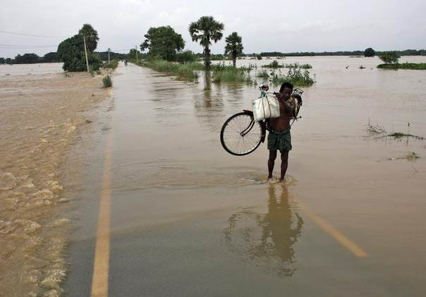 A man carries his bicycle through the flooded areas of Puri district after heavy monsoon rains in the eastern Indian state of Odisha August 8, 2014. REUTERS/Stringer