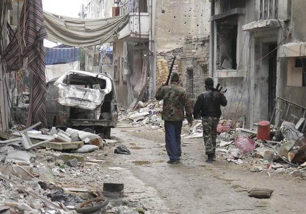 Free Syrian Army fighters walk past damaged buildings and vehicles in the besieged area of Homs January 22, 2014