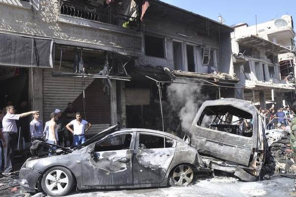 People gather around wreckage after a car bomb exploded in the Jaramana district of southeast Damascus July 25,2013, in this handout released by Syria's national news agency SANA. REUTERS/SANA/Handout