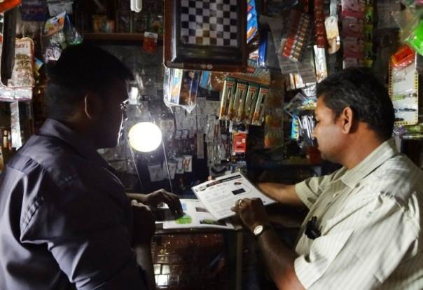 An Essmart Global representative trains a village shopkeeper on technology products that are helping improve life for poor rural communities and small scale-farmers in Coimbatore district, Tamil Nadu, India. Photo taken by Essmart Global in 2012