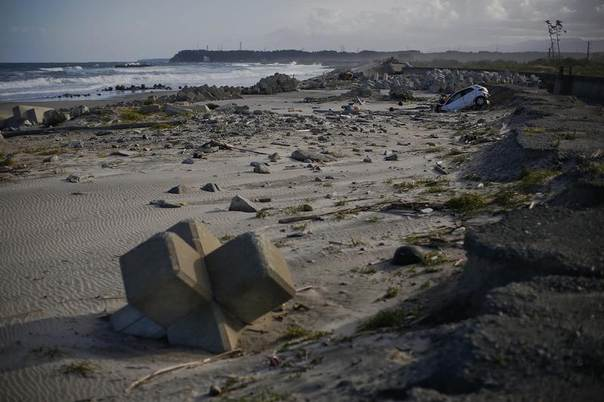 With cranes and chimneys of the crippled Daiichi nuclear power plant in the background, a beach littered with tsunami barriers, wreckages of cars and other debris is seen at coastal area of the evacuated town of Namie in Fukushima prefecture, Japan, September 23, 2013. REUTERS/Damir Sagolj