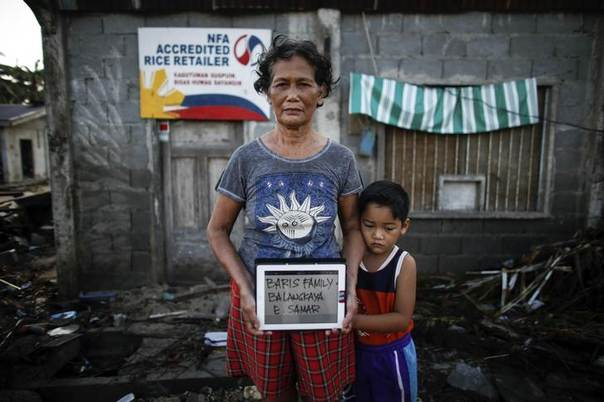 A couple of super typhoon Haiyan survivors pose with their names displayed on a tablet in Samar province in central Philippines November 11, 2013. REUTERS/John Javellana