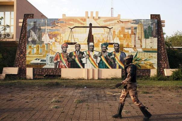 A gendarme walks past a mural outside the parliament building in Bamako, Mali, February 19, 2014. REUTERS/Joe Penney