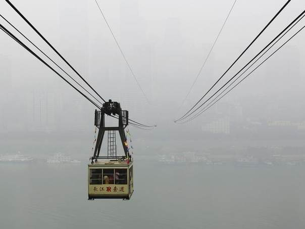 A cable car carrying passengers travels above the Yangtze River on a hazy day in Chongqing municipality, February 1, 2014. REUTERS/Stringer