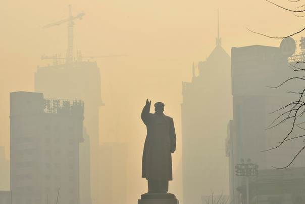 A statue of China's late Chairman Mao Zedong is seen in front of buildings during a hazy day in Shenyang, in China's Liaoning province, on May 7, 2013. REUTERS/Stringer