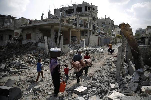 A Palestinian family carries their belongings towards the remains of their destroyed home after returning to Beit Hanoun town, which witnesses said was heavily hit by Israeli shelling and air strikes during the Israeli offensive, in the northern Gaza Strip August 5, 2014. REUTERS/Finbarr O'Reilly