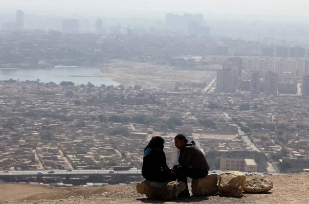 A couple sits on rocks as they talk in a hilly area overlooking Cairo on April 16, 2012. REUTERS/Asmaa Waguih
