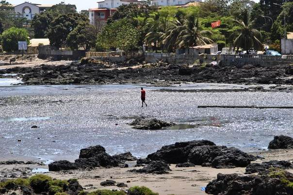 In this 2013 file photo, a man walks along the beach during low tide in Conakry REUTERS/Bate Felix
