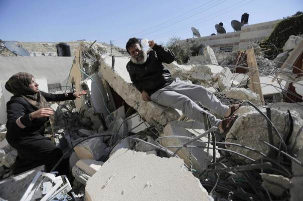 A Palestinian man reacts as he sits atop rubble after his home was demolished in Jabel Mukaber, a village in the suburbs of East Jerusalem February 5, 2014. REUTERS/Ammar Awad