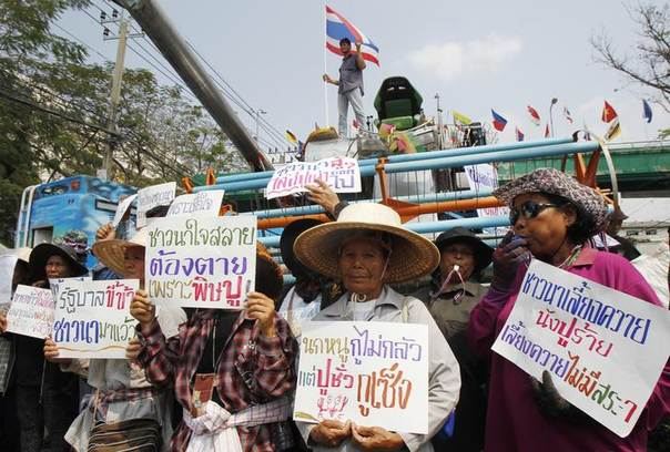 Farmers hold signs in front of a combine harvester during a rally demanding the Yingluck administration resolve delays in payment from the rice pledging scheme outside the Commerce Ministry in Nonthaburi province, on the outskirts of Bangkok February 6, 2014 The signs read,