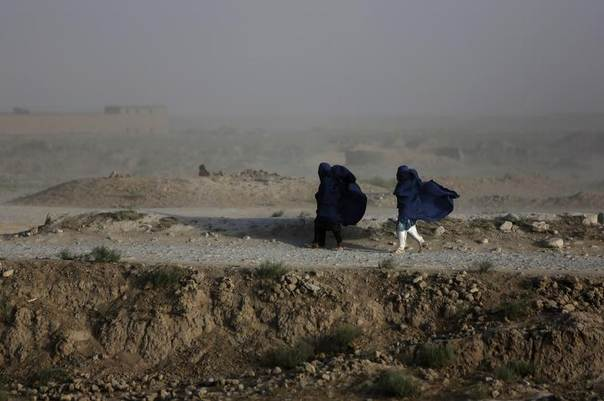 Women walk on a windy day outside Kabul, Afghanistan, July 23, 2013. REUTERS/Mohammad Ismail
