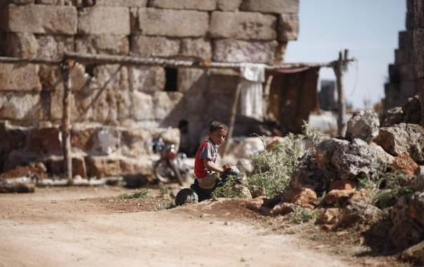 A child who has been displaced by fighting plays beside the ruins that are his makeshift home at the Shinshrah archaeological site, Idlib countryside, Syria, May 18, 2014. REUTERS/Nour Kelze
