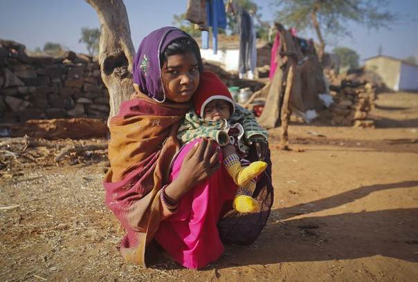 Krishna, 14, sits with her baby in her village in the northwestern state of Rajasthan. She married her husband when she was 11. The legal age for marriage in India is 18, but child marriages are common in poor, rural areas. Picture taken January 2013. REUTERS/Danish Siddiqui