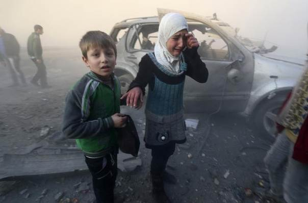 A girl cries near a damaged car at a site hit by what activists said were barrel bombs dropped by government forces in Aleppo's Dahret Awwad neighbourhood January 29, 2014. REUTERS/Saad AboBrahim