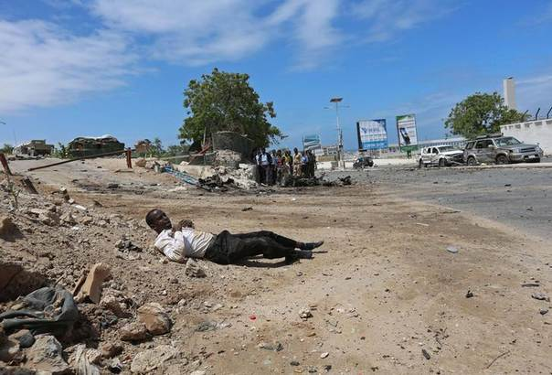 An injured member of staff of Somalia's Parliament lies on the ground during an attempted attack by Al Shabaab militia in Mogadishu May 24, 2014. REUTERS/Feisal Omar