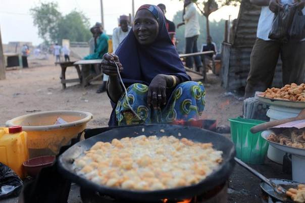 A woman fries beancakes on a street before the break of fast on the second day of the holy month of Ramadan in Nigeria's northern city of Kano, July 21, 2012. REUTERS/Akintunde Akinleye