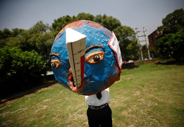 A boy holds a globe, that depicts the effects of global warming, while he returns from a rally organized to mark World Environment Day in Kathmandu on June 5, 2012. REUTERS/Navesh Chitraka