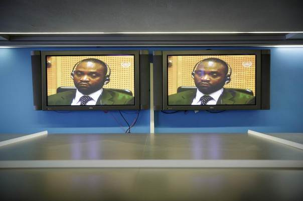 Congolese warlord Germain Katanga is seen on the television screens in the pressroom of the International Criminal Court (ICC) during his trial in The Hague, Netherlands, March 7, 2014. REUTERS/Phil Nijhuis/Pool