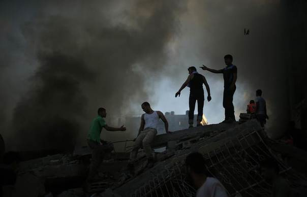 Palestinians try to extinguish a fire following what witnesses said was an Israeli air strike on a building in Gaza City July 24, 2014.  REUTERS/Suhaib Salem