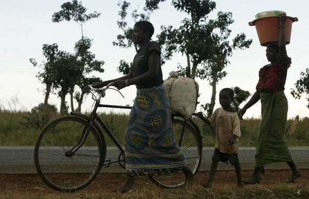 A mother and child transport a bag of maize meal on a bicycle along the highway linking Malawi to eastern Zambia. Picture April 21, 2008, REUTERS/Siphiwe Sibeko(Malawi)