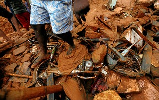 A man stands on a damaged bike at the site of a landslide in Bellana village, Sri Lanka