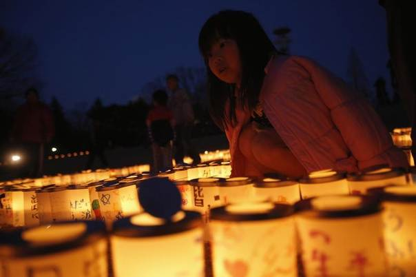 A girl looks at candles during a candlelight memorial held in remembrance of victims of the March 11, 2011 earthquake and tsunami, in Iwaki, Fukushima prefecture, Japan, March 9, 2014. REUTERS/Toru Hanai