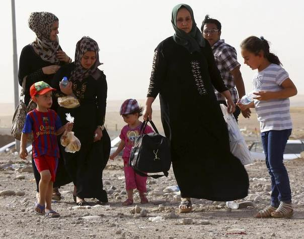 A family fleeing the violence in Mosul waits at a checkpoint on the outskirts of Arbil, in Iraq's Kurdistan region, June 11, 2014. REUTERS/Stringer