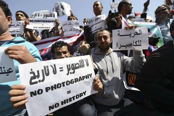Photojournalists hold up placards as they protest against harassment during news coverage, in front of the Shura Council in Cairo March 19, 2013. REUTERS/Khaled Desouki/