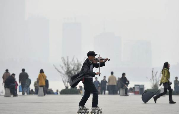 A man plays violin as he roller-skates on a square on a hazy day in Nanjing, Jiangsu province, Dec. 5, 2013. REUTERS/China Daily
