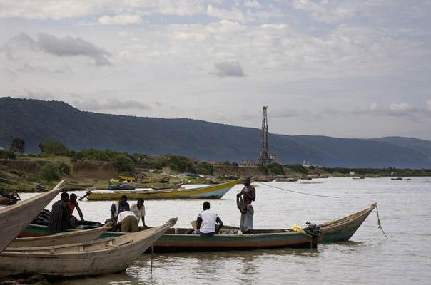 Fishermen row their boats next to an oil exploration site in Bulisa district, approximately 244 km (152 miles) northwest of Kampala in this undated handout photo from Tullow Oil Uganda, received by Reuters July 4, 2012 REUTERS/Tullow Oil Uganda/Handout