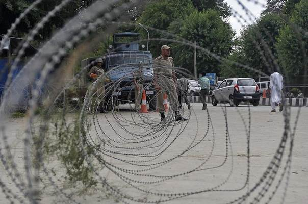 An Indian policeman stands guard next to concertina wires during a strike in Srinagar July 4, 2014. REUTERS/Danish Ismail