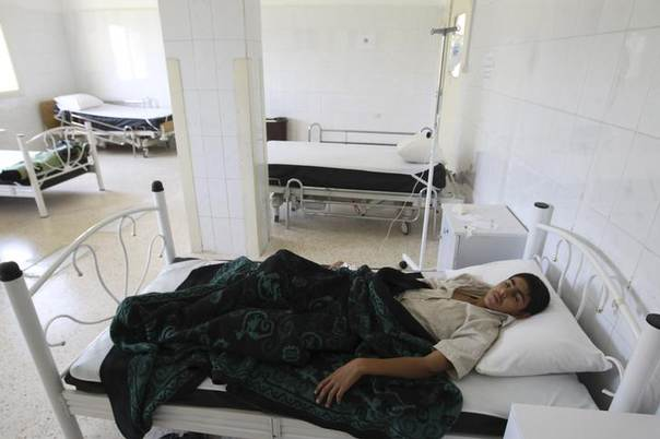A boy suffering from typhoid fever, caused by polluted water, lies in a hospital bed in al-Qouniya village in Syria's Idlib region. Picture May 27, 2013, REUTERS/Muzaffar Salman