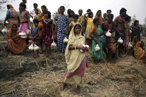Villagers displaced from their homes by a tidal wave caused by cyclone Aila collect food handed out by members of an NGO in Sundarbans delta, southeast of the east Indian city of Kolkata. Picture June 3, 2009, REUTERS/Parth Sanyal