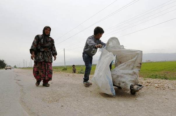 A Syrian refugee boy pushes a trolley loaded with hardware as his mother walks behind him in Bekaa valley. Picture April 11, 2013. REUTERS/Jamal Saidi