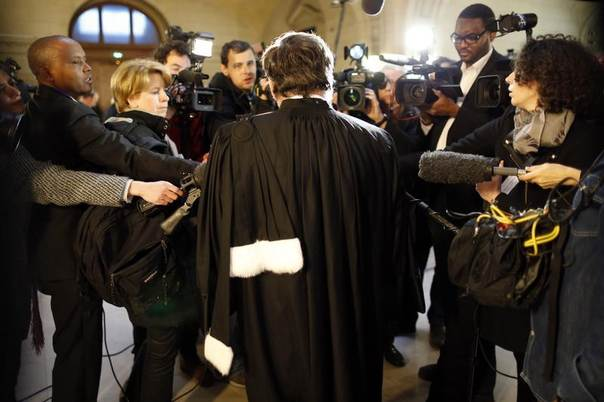 A lawyer speaks to the media as he arrives for the start of the trial of former Rwandan army captain Pascal Simbikangwa at a Paris court February 4, 2014. REUTERS/Charles Platiau