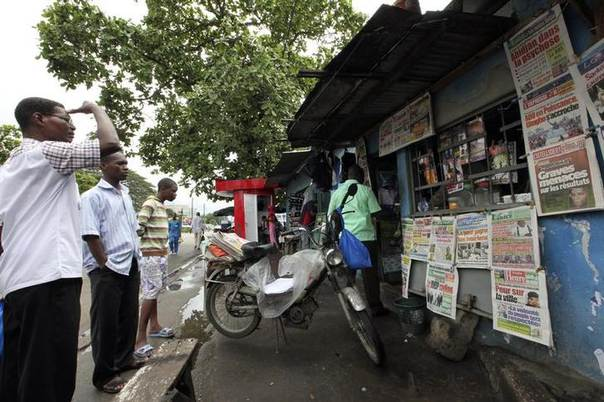 In this 2010 file photo, men read newspapers in Treichville, an area of Abidjan REUTERS/Luc Gnago