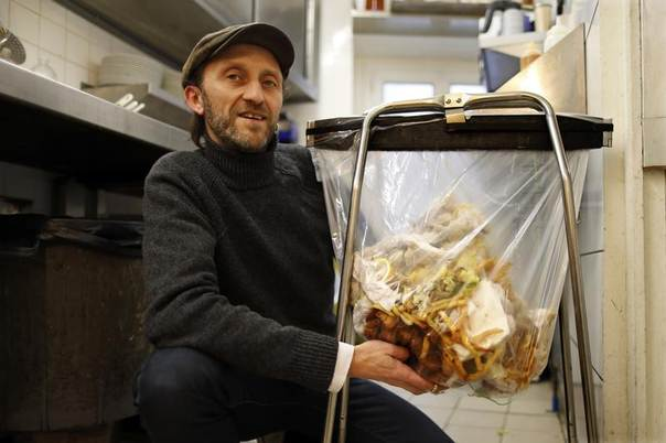 Stephan Martinez, owner of Le Petit Choiseuil bistrot, poses next to food waste garbage in the kitchen of his restaurant in Paris, Feb. 12, 2014. REUTERS/Charles Platiau