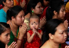 A girl offers prayers inside a Buddhist temple on the occasion of Buddha Purnima festival