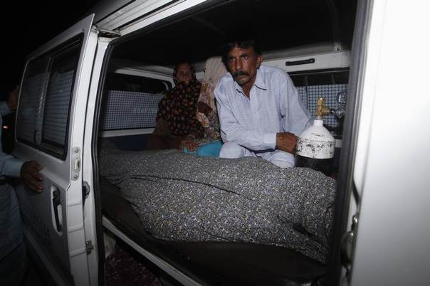 Mohammad Iqbal sits next to his wife Farzana's body, who was killed by family members, in an ambulance outside of a morgue in Lahore May 27, 2014 REUTERS/Mohsin Raza