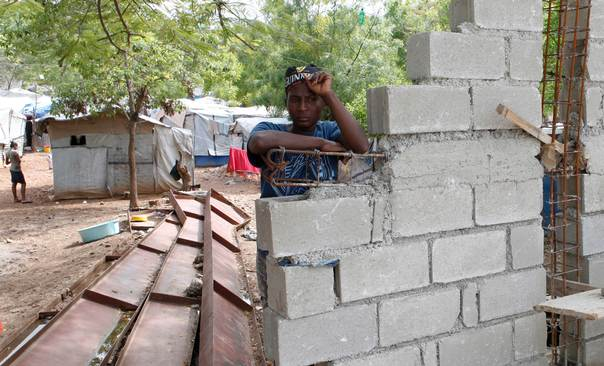 In a file photo from April 2013, Haitian woman Romaine, one of the thousands made homeless by the 2010 earthquake, leans on a wall being built by the owners of the land where she lives in Shelter Camp 3, one of 385 informal tent cities that was still in existence after the disaster, in the Delmas suburb of Port-au-Prince. At the time the photo was taken, Camp 3 sheltered 86 families who said they lived in perpetual fear of forced eviction by the landowners, who had recently sent agents to launch a series of attacks and were building a wall around the camp. REUTERS/Marie Arago
