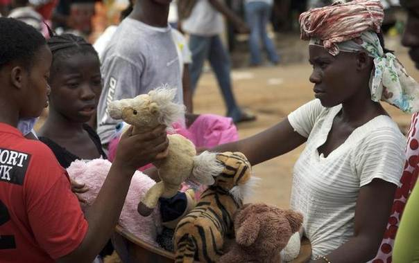 A woman sells toys at a market in the Liberian capital Monrovia May 4, 2010. REUTERS/Tim Cocks