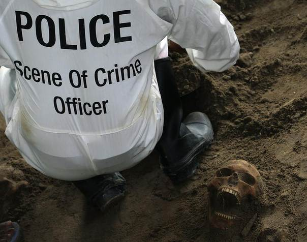 A police officer works next to a human skull at a construction site in the former war zone in Mannar, about 327 km (203 miles) from the capital Colombo, January 16, 2014 REUTERS/Dinuka Liyanawatte