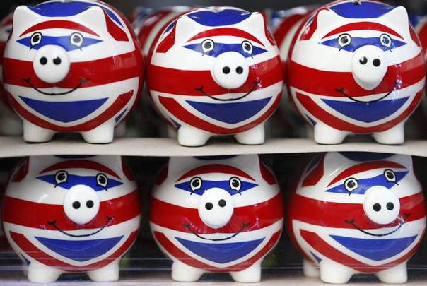 Smiling Union Jack piggy banks are lined up for sale in the window of a souvenir store on Oxford Street in central London January 20, 2014 REUTERS/Andrew Winning