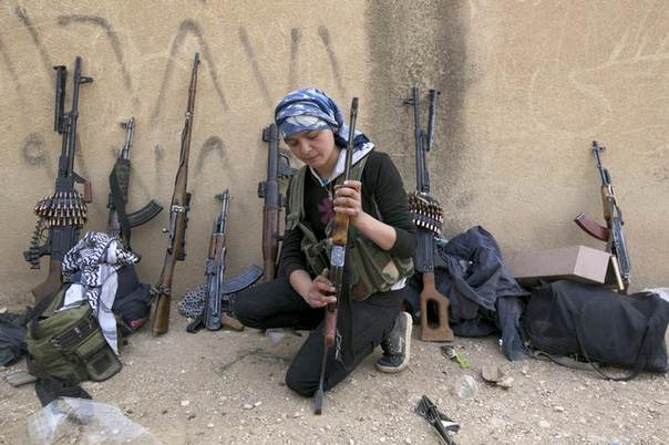 A Kurdish female fighter from Kurdish People's Protection Units (YPG) checks her weapon near Ras al-Ain, in the province of Hasakah, after capturing it from Islamist rebels November 6, 2013. REUTERS/Stringer