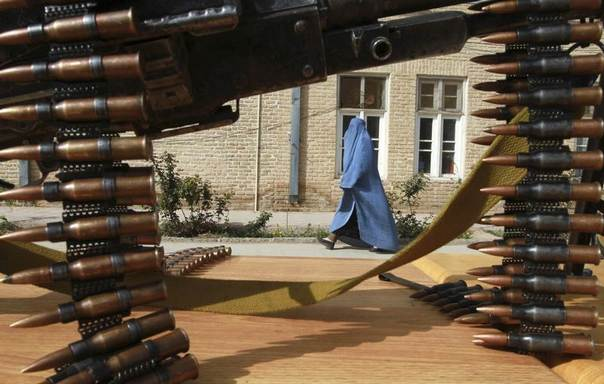 An Afghan woman walks inside a police compound as former Afghan Taliban members hand over their weapons after joining the Afghan government's reconciliation and reintegration programme in Herat province, Afghanistan, March 19, 2013. REUTERS/Mohmmad Shoib