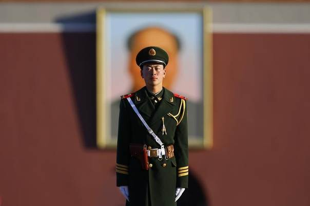 A paramilitary policeman stands guard in front of a portrait of China's late leader Mao Zedong near the Great Hall of the People at Tiananmen Square during the opening session of the National People's Congress (NPC) in Beijing, March 5, 2014. REUTERS/Petar Kujundzic