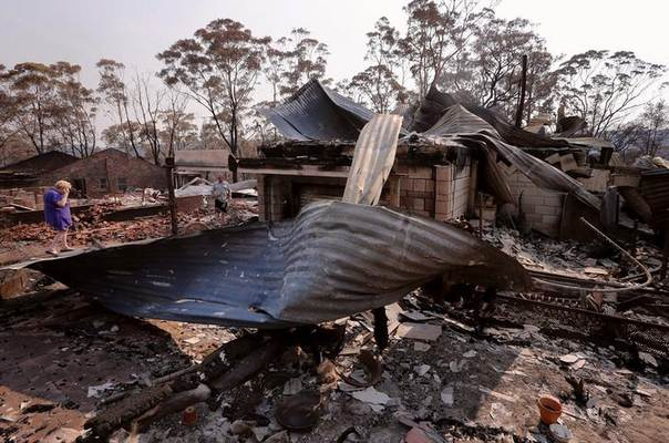 Local resident Delia Smith reacts as she inspects her family's house with her husband Colin after it was destroyed by a bushfire in the Blue Mountains suburb of Winmalee, located around 70 km west of Sydney, October 21, 2013. REUTERS/David Gray